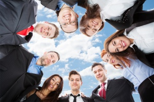 Multiethnic Businesspeople Forming Huddle Against Sky